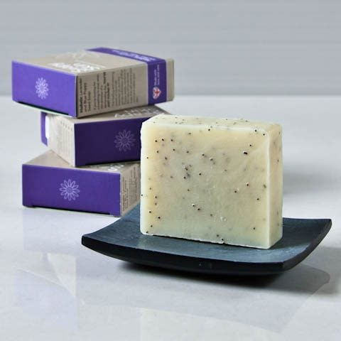 Soapy Skin natural handmade lavender and blue poppy seed soap on a soap dish with boxes stacked at the side
